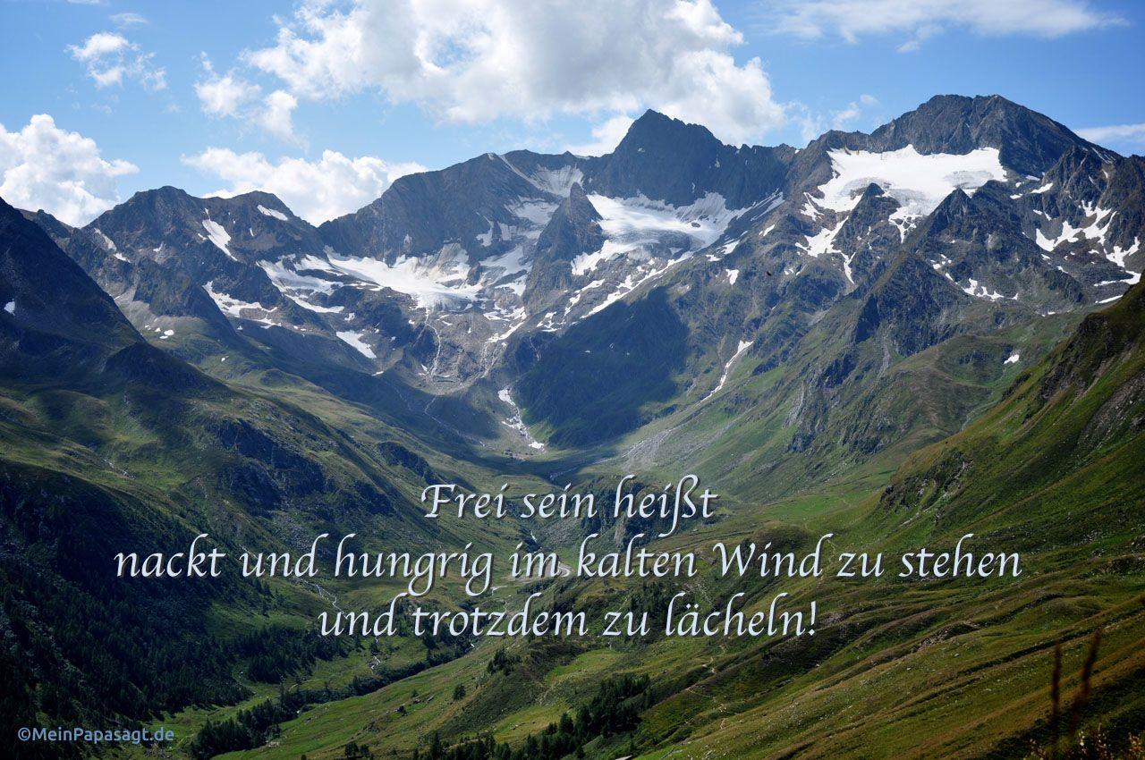 Bergpanorama mit dem Spruch: Frei sein heißt nackt und hungrig im kalten Wind zu stehen und trotzdem zu lächeln!