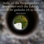 Loch im Stein mit Blick auf weißen Stein und Baum mit dem Einstein Zitat: Mehr als die Vergangenheit interessiert mich die Zukunft, denn in ihr gedenke ich zu leben. Albert Einstein