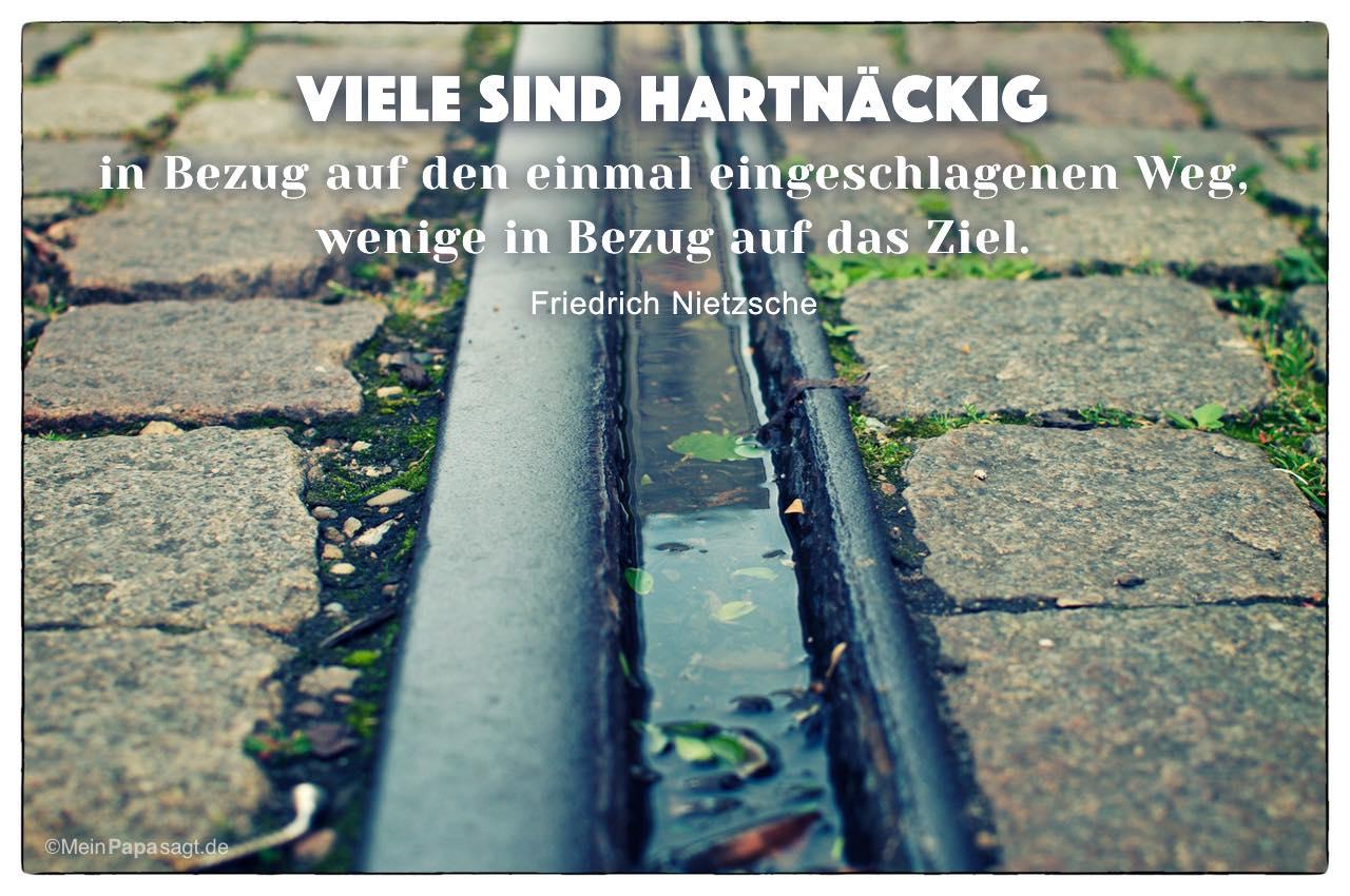 Gleise mit dem Friedrich Nietzsche Zitat: Viele sind hartnäckig in Bezug auf den einmal eingeschlagenen Weg, wenige in Bezug auf das Ziel. Friedrich Nietzsche