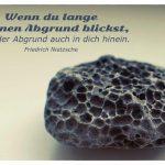 ausgespülter Stein mit dem Nietzsche Zitat: Wenn du lange in einen Abgrund blickst, blickt der Abgrund auch in dich hinein. Friedrich Nietzsche