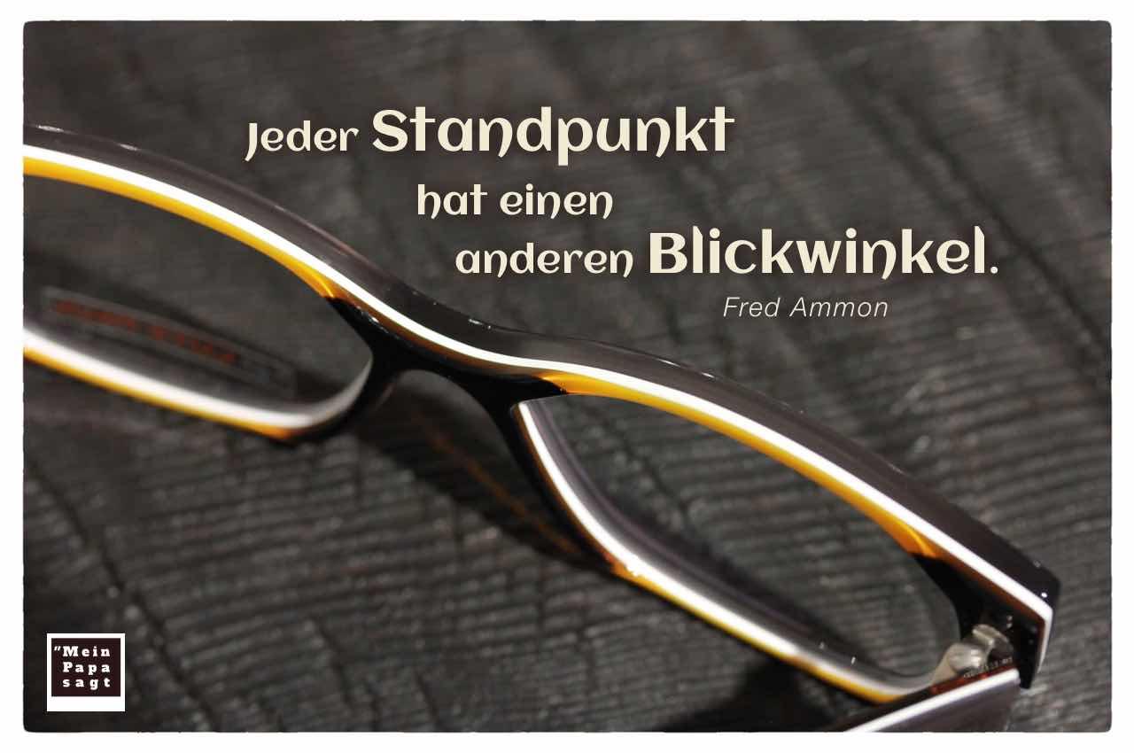 Brille auf Holztisch mit dem Ammon Zitat: Jeder Standpunkt hat einen anderen Blickwinkel. Fred Ammon